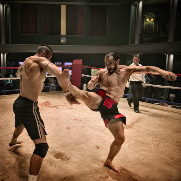 Scott Adkins blocks a kick from Tim Man in Boyka: Undisputed.